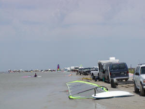 Smaller RVs and vehicles parked all along the shoreline